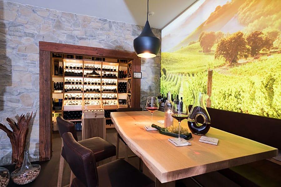 Weinkeller, Eiche, Tisch mit Waldsaum, beleuchtete Glasrückwand,